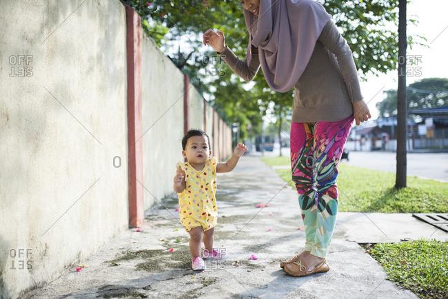 Cute baby girl walking on sidewalk as mother supervises