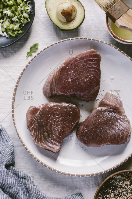 Three pieces of fresh yellow fin tuna are brushed with olive oil and seasoned with salt and pepper