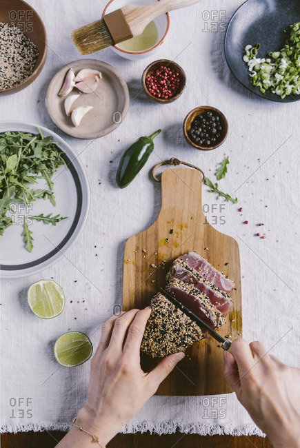 Woman slicing a sesame crusted and seared yellow fin tuna on a wooden board