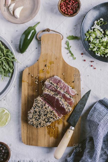 A piece of sesame crusted seared tuna sliced on a cutting board