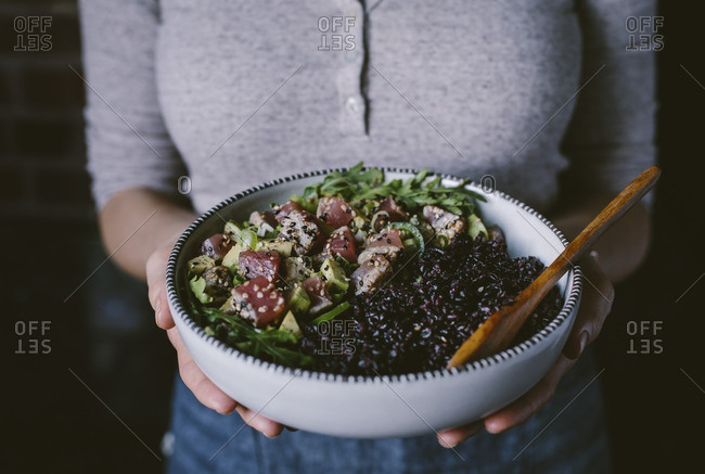 Woman holding a bowl filled with sesame crusted seared tuna salad and forbidden rice