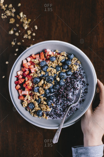 Woman preparing to eat bowl of forbidden rice morning cereal with berries