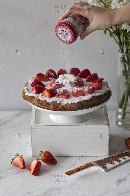 Strawberry cake with whipped coconut cream and topped with fresh strawberries being dusted with powdered sugar