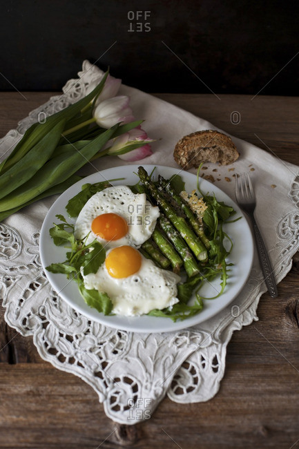 Roasted asparagus with parmesan cheese on a bed of rucola salad topped with fried eggs