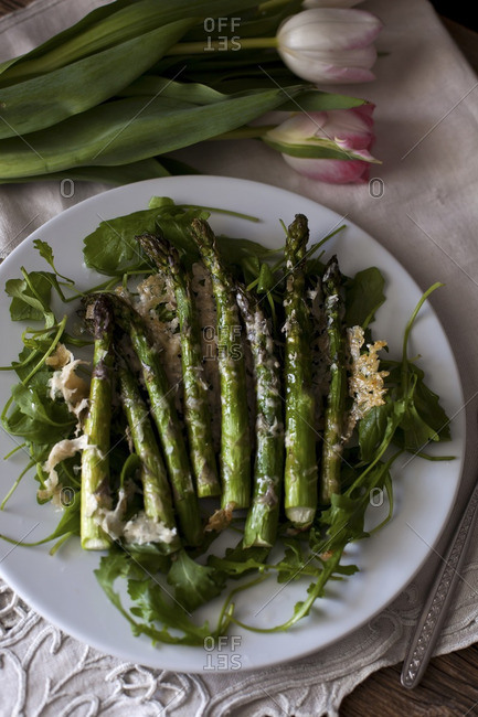 Roasted asparagus with parmesan cheese on a bed of rucola salad