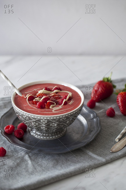 Strawberry and raspberry smoothie topped with fresh berries and cashew butter in a bowl