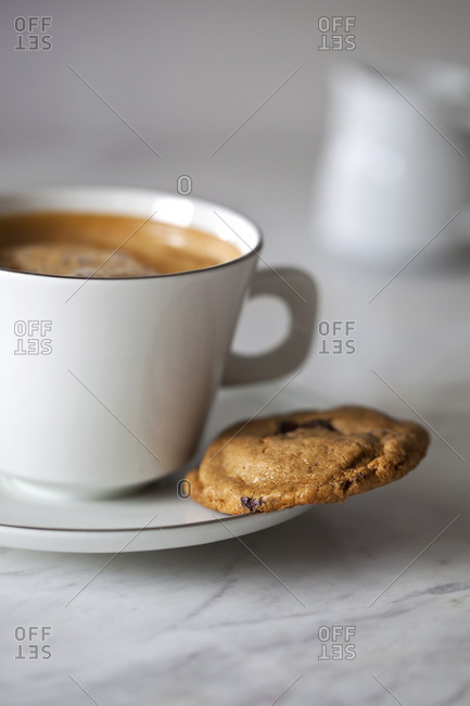 Peanut butter and chocolate cookie and a cup of coffee on a white marble table