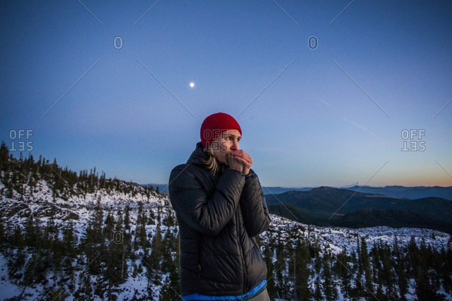 A young woman blows into her hands on a cold night while attempting to climb Mt St Helens in WA