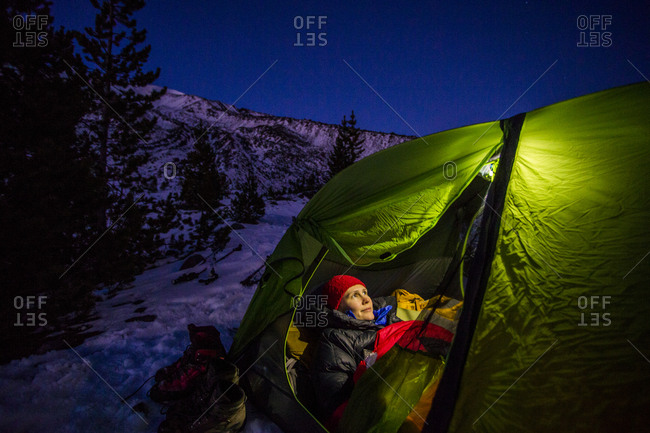 A young woman rests in a glowing tent at night while attempting to climb Mt St Helens