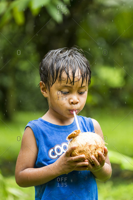 Young Asian boy drinking from tropical Coconut in rain storm, Costa Rica