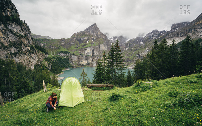 Young woman doing camping in Oeschinensee, Bern, Switzerland