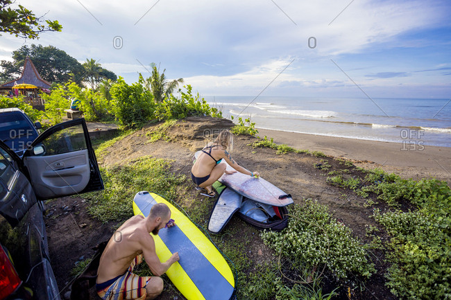 Young surfers are waxing their boards before surf session