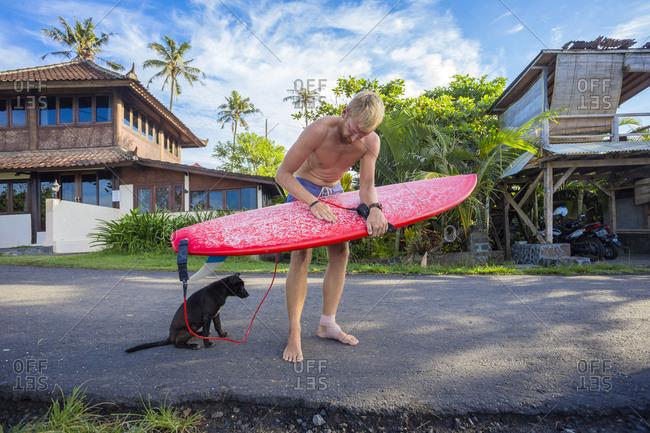 Surfer is waxing a board