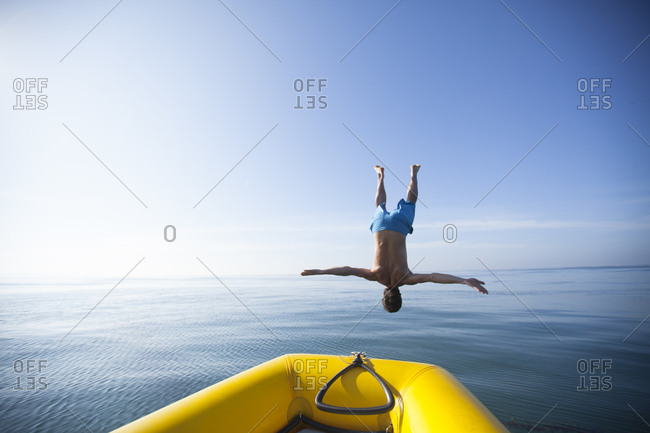 Adult man doing a backflip off of an inflatable boat into the ocean