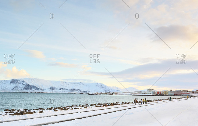People walking along waterfront in village in Iceland