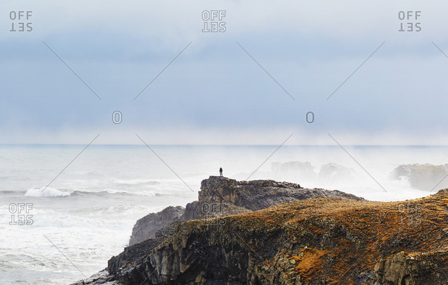 Silhouetted person on seaside cliffs in Iceland