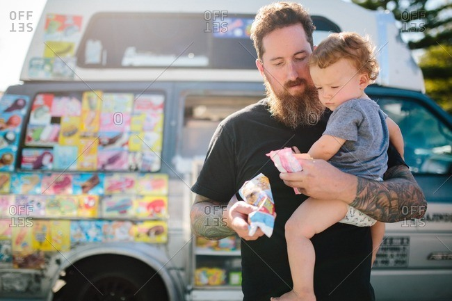 Dad carries child with ice cream from ice cream truck