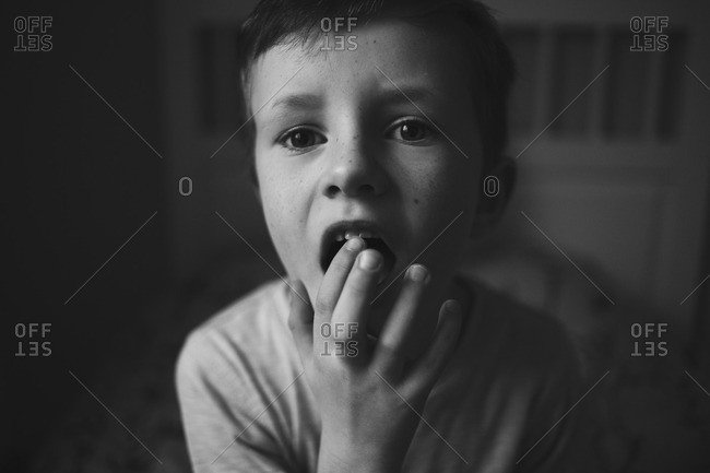 Portrait of a boy touching his front tooth