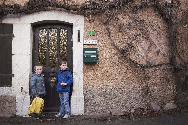 Two boys standing outside a doorway holding backpacks