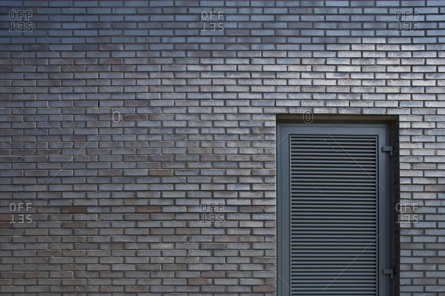 Close-up of door set in to a brick wall
