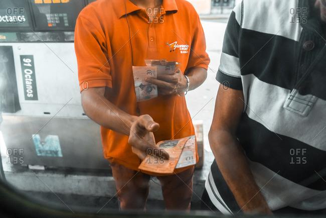Venezuela - April 19, 2016: Gas station attendant making change for customer, Venezuela