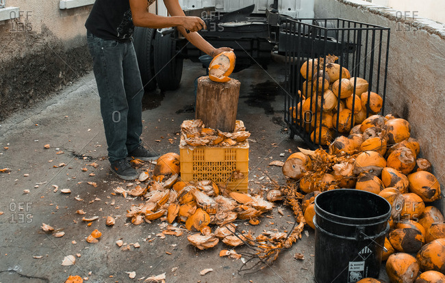 Man cutting coconuts with machete in alleyway