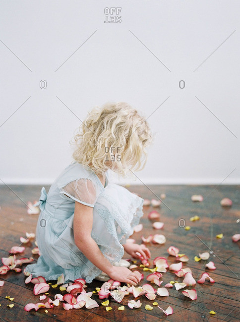 Little girl sitting among rose petals scattered on the floor