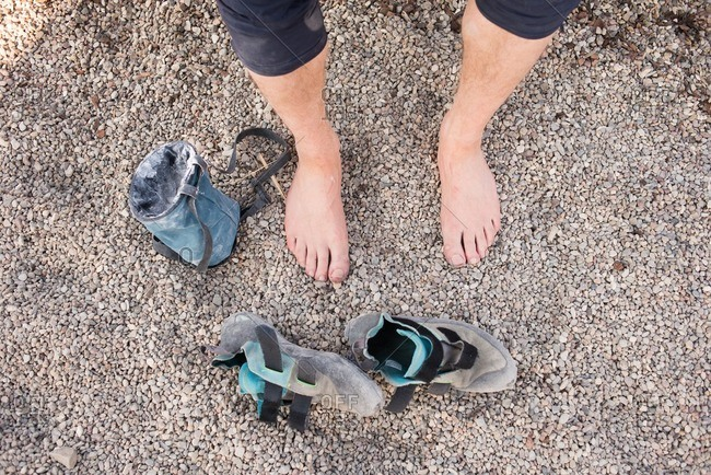 Overhead view of climbing shoes next to a man's barefeet