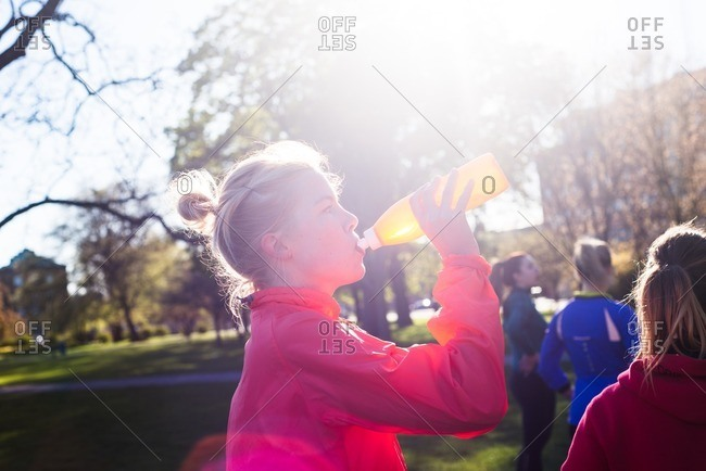 Woman drinking from a water bottle during an outdoor workout