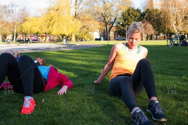 Women sitting on the grass resting after a workout