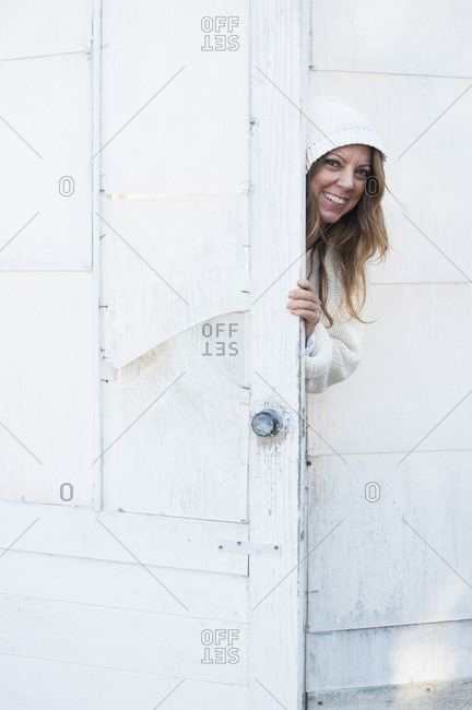 Woman peeking out from behind the door of a white wood outbuilding