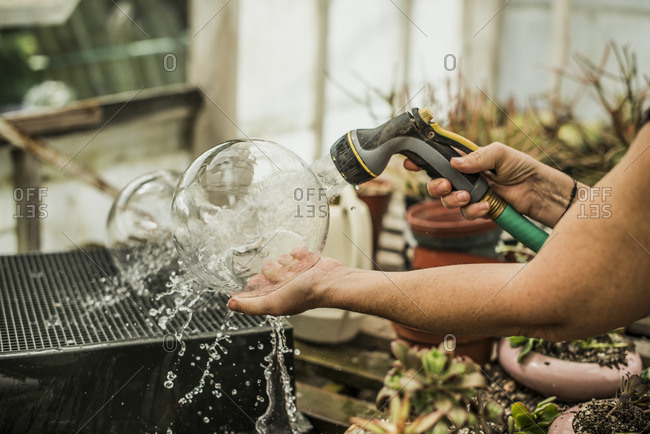 Woman rinsing out glass terrariums on a workbench