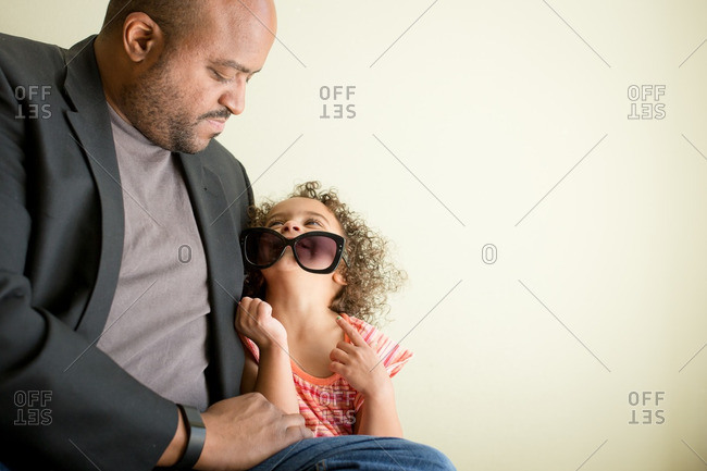 Playful young girl looks up adoringly at her father