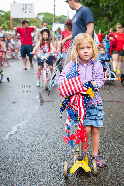 Girl riding scooter decorated with the American flag in a parade