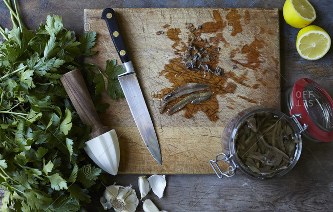 Cutting board with parsley, lemon and anchovies
