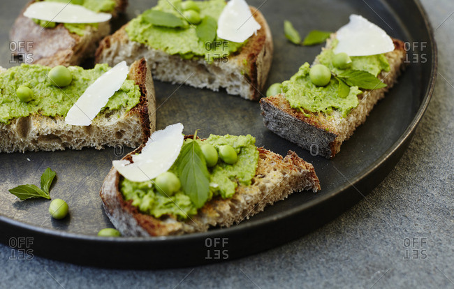 Close-up of crostini with green pea spread with cheese