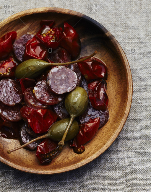Bowl with roasted tomatoes with sliced sausage and capers