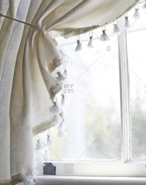 Close-up of white curtains with tassel trim on window