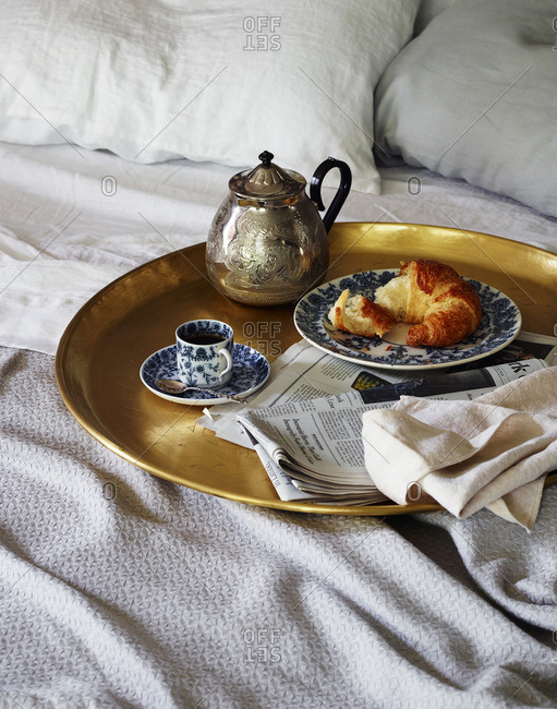 Brass tray with teapot and cup of tea with croissant and news paper on bed