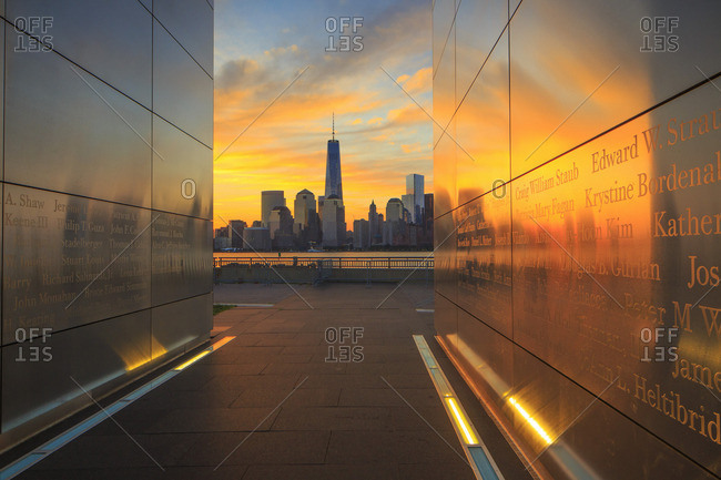 Empty Sky 9/11 memorial in Liberty State Park with Freedom Tower and Lower Manhattan in the background at sunrise