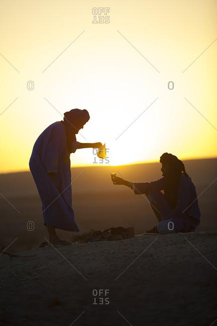 Arab men drinking tea in the desert at sunrise