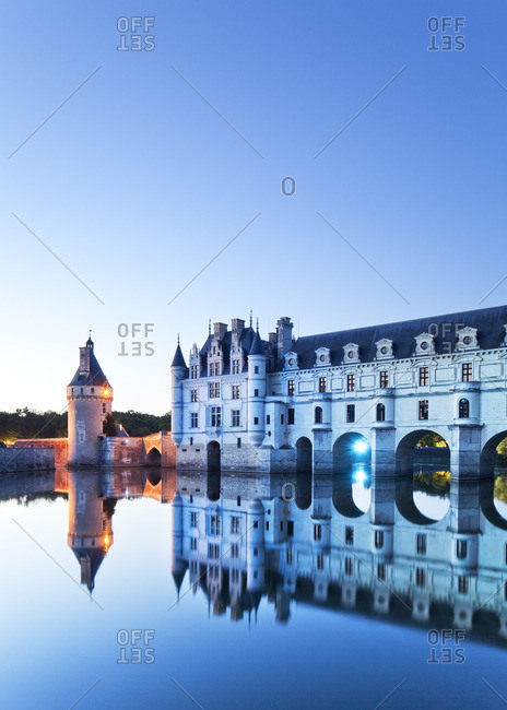 The chateau Chenonceau on the river Cher lit at dusk