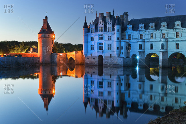 The chateau Chenonceau on the river Cher illuminated at dusk