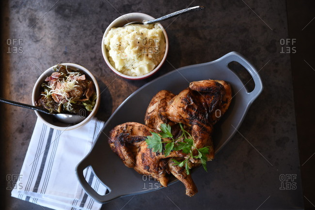 Overhead view of a platter of grilled chicken served with mashed potatoes and roasted Brussels sprouts