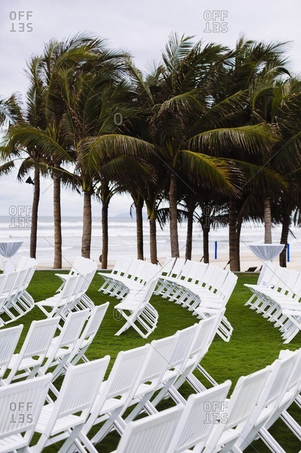 Empty white chairs set up on a lawn for a beach wedding in Southeast Asia