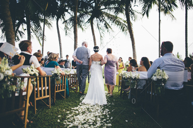 April 29, 2016: Bride walks down the aisle with her parents at an outdoor wedding in Hoi An, Vietnam