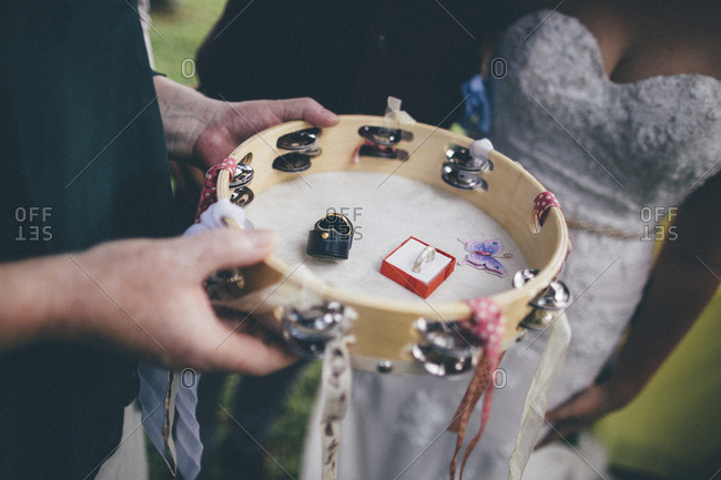Bride and groom standing next to a man holding a tambourine containing two wedding rings