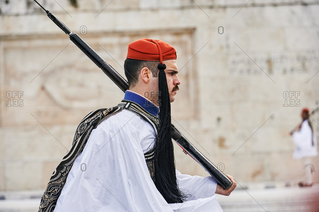 Athens, Greece - March 27, 2016: Greek solider marching in front of the Tomb of the Unknown Solider during the changing of the honor Evzones guards ceremony in front of the Parliament Building in Syntagma Square, Athens, Greece.