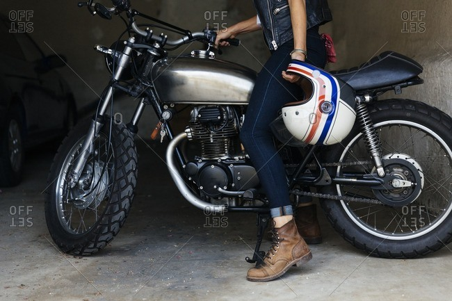 Woman sitting on a motorcycle in a garage