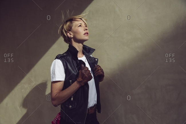 Woman standing against a wall and looking up